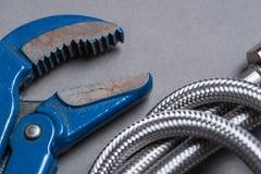 Regelbare moersleutel en de gevlechte slang van het roestvrij staalwater Royalty-vrije Stock Foto's