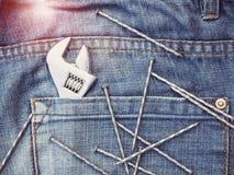 Regelbare moersleutel, spijkers en modieuze jeans Hoogste mening stock afbeeldingen