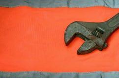 Regelbare moersleutel tegen de achtergrond van een oranje overhemd van de signaalarbeider Stilleven verbonden aan reparatie, spoo royalty-vrije stock foto
