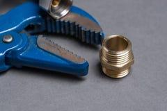 Regelbare moersleutel, uitsteeksel en de gevlechte slang van het roestvrij staalwater Stock Afbeelding
