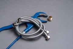 Regelbare moersleutel, uitsteeksel en de gevlechte slang van het roestvrij staalwater Royalty-vrije Stock Afbeelding