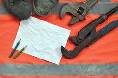 Regelbare moersleutels met oude laarzen en een blad van document met twee potloden Stilleven verbonden aan reparatie, spoorweg of royalty-vrije stock foto's