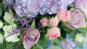 Regeling van verschillende bloemen die van verschillende kleuren, zich op lijsten voor een vakantiedecoratie bevinden stock video