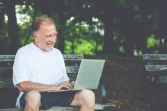 Regelmäßiger alter Kerl, der auf Computer schreibt lizenzfreie stockbilder