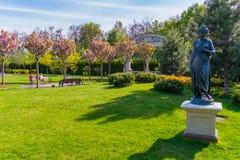 Regelmatig in orde gemaakt gazon met een beeldhouwwerk van een vrouw tegen de achtergrond van groene bomen royalty-vrije stock afbeeldingen