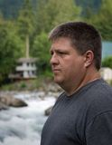 Regelmatige kerel die en dichtbij de rivier mediteert denkt stock afbeeldingen