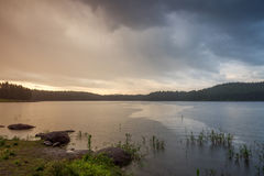 Regen über dem See bei Sonnenuntergang Stockfotos