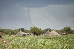 Regen, der nahe Hütten in Südsudan fällt Stockbild