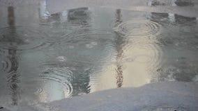 Regen die op bestrating bij lopende mensen en drijfauto's vallen stock footage