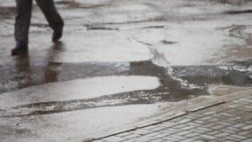 Regen die op bestrating bij lopende mensen vallen stock video