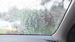 Regen die op het windscherm van het autoraam druipen stock footage