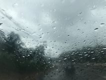 Regen drohardly, zum eines Autos in der Front zu sehen und Bäume entlang der Straße lizenzfreie stockfotos