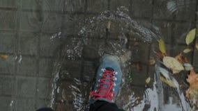 Regen en vulklei, die in leerschoenen lopen stock videobeelden