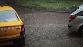 Regen het gieten neer op bestrating, een taxi en een auto wordt vloed Een andere auto gaat over door, rond bespat het water onder stock video
