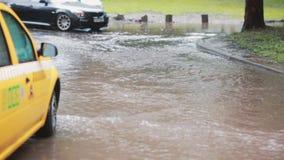 Regen het gieten neer op bestrating en van een taxiauto draaien in vloed stock videobeelden