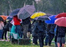 Regen, Leute, die ein jugendliches Spiel des Schlammes und des Regens gerade aufpassen, um ihren Kindern zu folgen lizenzfreie stockfotografie