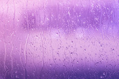 Regen op een venster in purpere kleuren stock afbeelding