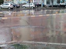 Regen produziert Löcher im Asphalt Stockfotos