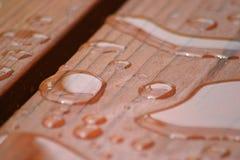 Regen-Tropfen auf Rotholz stockfoto