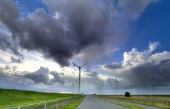 Regen und blauer Himmel über Windkraftanlagen und Straße stockfotografie