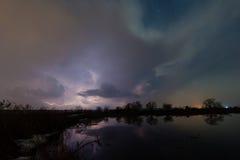 Regen und Blitz über dem Fluss Stockbild