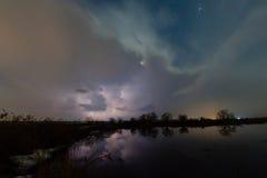 Regen und Blitz über dem Fluss Stockfotografie