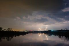 Regen und Blitz über dem Fluss Stockfoto