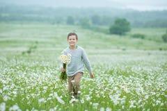 Regen und Sonnenschein mit einem lächelnden Jungen, der einen Regenschirm und einen Betrieb durch eine Wiese des Wildflowers dund Stockfoto