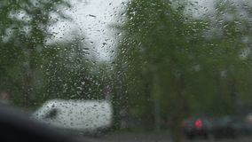 Regenachtig en winderig weer tijdens een orkaan en een hagel - bekijk van een warme auto door het windschermvenster met regendali stock videobeelden