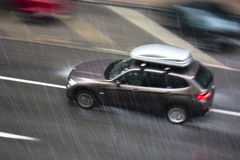 Regenachtige dag in de stad: Een drijfauto in de straat die door wordt geraakt hij Stock Foto