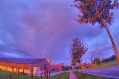 Regenbogen über dem Bauernhof Stockbild