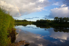 Regenbogen über dem Fluss Stockbild