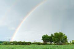 Regenbogen über dem grünen Feld Landschaftshintergrund Lizenzfreie Stockbilder