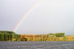 Regenbogen über dem See in Südwales Stockbild