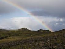 Regenbogen über den Bergen von Island, bedeckt mit grünem Moos Stockfotos