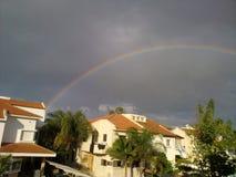 Regenbogen über den Häusern Stockbilder