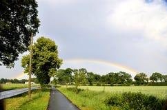 Regenbogen über den Kronen der Bäume nahe bei dem Fahrradpfad Stockbild