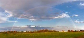 Regenbogen über der grünen Wiese und den Wolken der Himmel Lizenzfreie Stockfotografie