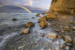 Regenbogen über der Klippe, nachdem ein Abendsturm geführt worden ist Stockbilder
