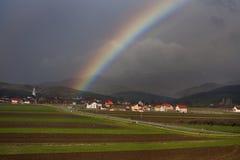 Regenbogen über Dorf und Ackerland Stockbild