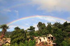 Regenbogen über einem kleinen hani Dorf Lizenzfreie Stockfotos