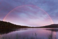 Regenbogen über einem kleinen See Stockbild