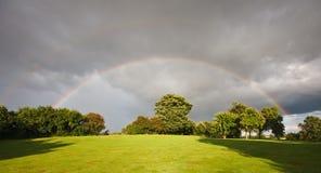 Regenbogen über einem Obstgarten am Sommer lizenzfreies stockbild