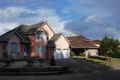 Regenbogen über einem rosafarbenen Haus Lizenzfreies Stockbild