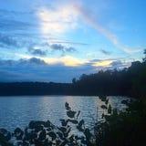Regenbogen über einem See Lizenzfreies Stockfoto