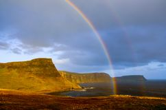 Regenbogen über einer drastischen Küstenlinie von schottischen Hochländern, Insel von Skye, Großbritannien Lizenzfreies Stockfoto