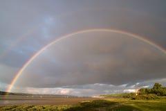 Regenbogen über Fluss Stockbild