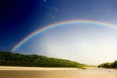 Regenbogen über Fluss stockfotos