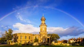 Regenbogen über Kirche Stockfotografie