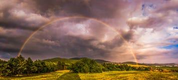 Regenbogen über Landschaft bei Sonnenuntergang Stockfoto